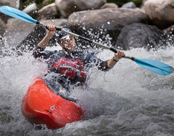 A canoeist paddleing against white water rapids